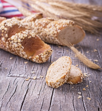 unsliced: Two home rye baguette with honey oat flakes on a simple gray wooden background with golden ripe ears. selective Focus