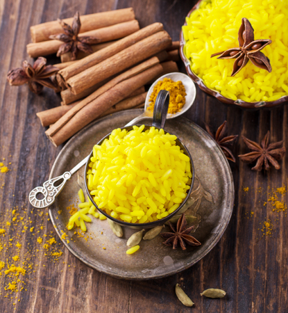food background: Bright yellow boiled rice with turmeric and aromatic spices on a dark wooden background in old vintage metal bowl. selective Focus
