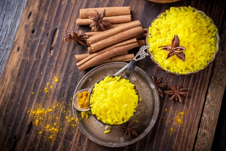 food background: Bright yellow boiled rice with turmeric and aromatic spices on a dark wooden background in old vintage metal bowl Stock Photo