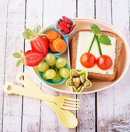 tomate cherry: Lunch box for kids with fresh vegetables, fruits, nuts, berries and sandwich with cheese and herbs on a simple white wooden background. selective Focus