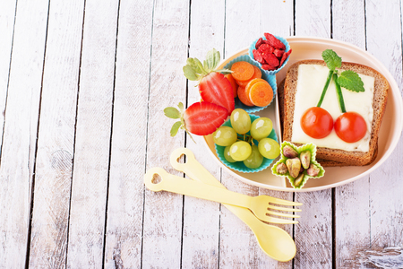 Lunch box for kids with fresh vegetables, fruits, nuts, berries and sandwich with cheese and herbs on a simple white wooden background. selective Focus 版權商用圖片 - 50011716
