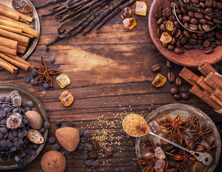 Coffee beans, chocolate drops, vanilla pods, cinnamon sticks, anise stars and brown sugar in a vintage silver cups on a dark textural wooden background. selective Focus Stock Photo