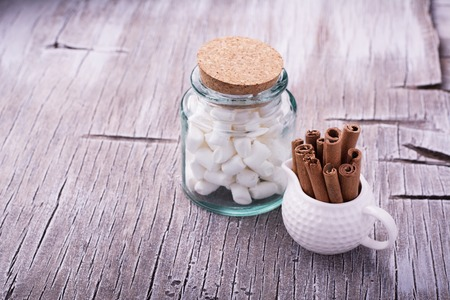 creamer: A handful of cinnamon sticks in a white ceramic jar with creamer and marshmallow for winter hot drink on a light wooden background. selective Focus