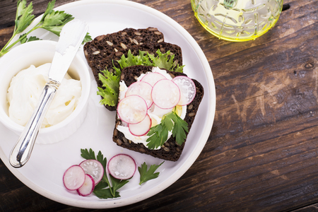 cream cheese: Healthy sandwiches for breakfast or snack dark grain bread with curd cream cheese, radish, herbs on the white ceramic plate on a wooden background. selective Focus Stock Photo