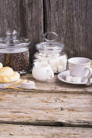 creamer: Morning still-life in the kitchen during breakfast with a jar of coffee beans, sugar cubes, fresh homemade cakes, cup and creamer. Ideas of storage in the kitchen, healthy home cooking. selective Focus Stock Photo