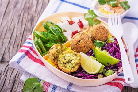 Box Lunch on the road for a picnic or to the office for lunch with cous cous, falafel chick peas, red cabbage salad, slices of cucumber, feta cheese and salad hummus in a white plastic container with a fork and spoon decorated with sprigs of cilantro. sel