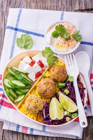 sel: Box Lunch on the road for a picnic or to the office for lunch with cous cous, falafel chick peas, red cabbage salad, slices of cucumber, feta cheese and salad hummus in a white plastic container with a fork and spoon decorated with sprigs of cilantro. sel