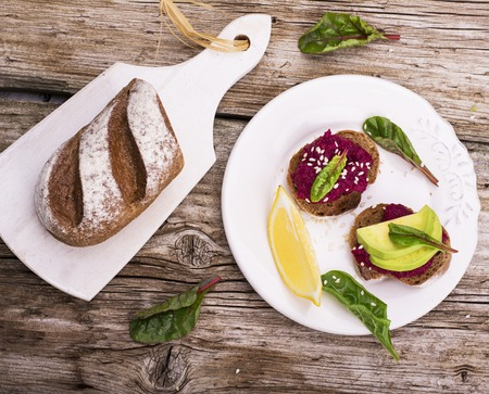 sesame seeds: Sandwiches for breakfast or snack of hummus with roasted beets and chickpeas with avocado, lemon juice, juicy fresh chard and grain bread and white sesame seeds. The concept of healthy natural foods. Stock Photo