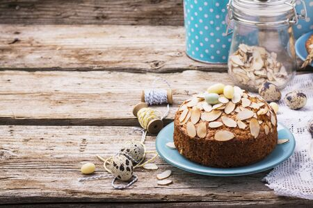 setting table: Simple homemade pecan pie decorated with petals of almond with a wooden background Serving Easter used blue and yellow colors, quail eggs, lavender flowers, vintage linen tablecloth handmade. Stock Photo