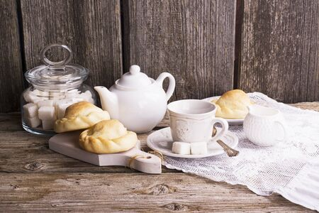 home cooking: Morning still-life in the kitchen during breakfast with a jar of coffee beans, sugar cubes, fresh homemade cakes, cup and creamer. Ideas of storage in the kitchen, healthy home cooking. selective Focus Stock Photo