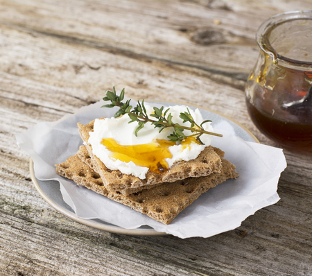 free dish: Snack gluten free crispbread with cream cheese honey and thyme on a simple ceramic dish on the kitchen table for a healthy family breakfast. selective Focus Stock Photo
