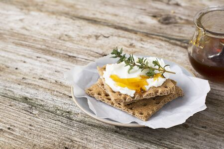 healthy snack: Snack gluten free crispbread with cream cheese honey and thyme on a simple ceramic dish on the kitchen table for a healthy family breakfast. selective Focus Stock Photo