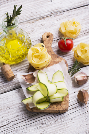 home cooking: Ingredients for cooking pasta with vegetables - spaghetti, zucchini, tomatoes, garlic, rosemary, pepper. The concept of simple home cooking with natural products. Selective focus Stock Photo