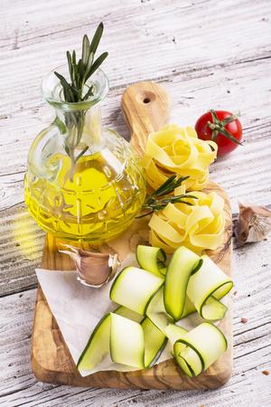 productos naturales: Ingredientes para cocinar pasta con verduras - espaguetis, calabacín, tomate, ajo, romero, pimienta. El concepto de casa sencilla de cocinar con productos naturales. enfoque selectivo