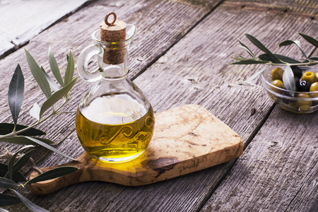 Kruik met extra vergine olijfolie op olijven snijplank omringd door takken van de olijfboom en olijven. Selectieve aandacht. Het concept van een gezonde natuurlijke voeding Stockfoto