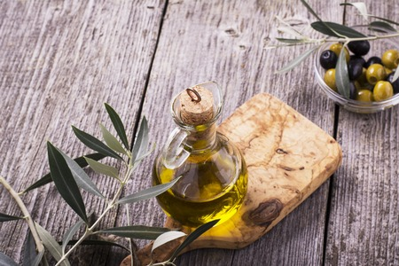 olive oil bottle: Jug with extra virgin olive oil on olive cutting board surrounded by branches of the olive tree and olives. Selective focus. The concept of a healthy natural food Stock Photo