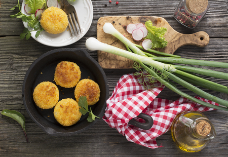 potato tree: Healthy vegetable dinner. Potato cutlets grilled with fresh vegetables herbs and olive oil for dinner on a dark wooden background in a black cast iron skillet. View from above Stock Photo