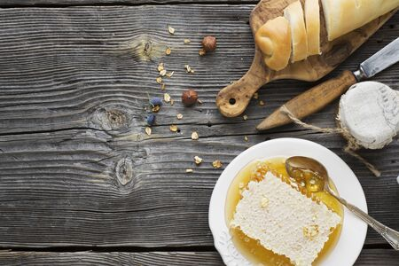 woody: Honey, slice of bread, on an old vintage planked wood table from above. Rural or rustic style breakfast concept. Background layout with free text space. Stock Photo