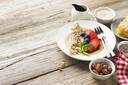 유행: 건강 한 아침 식사 추세. 초콜릿 크림 및 모듬 과일과 열매 딸기, 블루 베리, 치아 씨앗, 그라 놀라, 견과류와 꿀 미세 곡물 귀리 팬케이크. 유기 건강 식