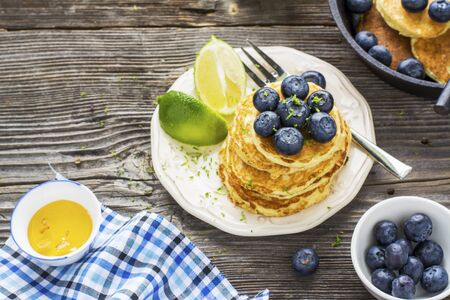 submission: Several domestic hot pancakes with fresh ripe blueberry lime zest, honey on a white plate in the batch submission to breakfast on a wooden dark background. selective focus