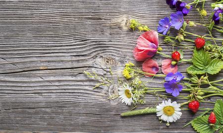 Fondo de flores de verano naturaleza muerta. Varias flores salvajes del campo del verano y fresas fragantes del bosque en un fondo de madera gris estructurado. Foto de archivo