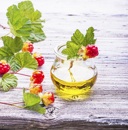 potbellied: A small glass jar with a rare northern cloudberry oil with berries and leaves on the gray wooden structural background. The concept of the use of rare natural oils useful plant