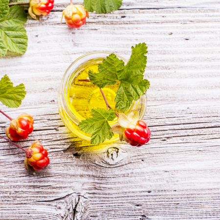 chicouté: A small glass jar with a rare northern cloudberry oil with berries and leaves on the gray wooden structural background. The concept of the use of rare natural oils useful plant