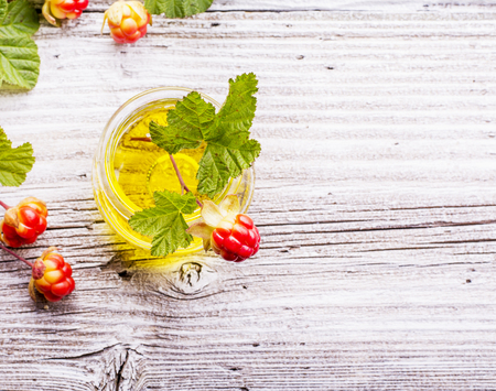 chicout�: A small glass jar with a rare northern cloudberry oil with berries and leaves on the gray wooden structural background. The concept of the use of rare natural oils useful plant