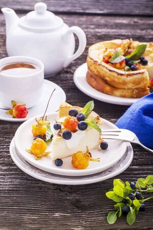 chicouté: Homemade breakfast. Fresh cheesecake with Nordic berries cloudberries and blueberries in plain wooden background served with cloudberry tea in a white ceramic bowl. Decorated branches forest blueberries
