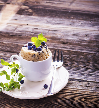 homemade cake: Healthy breakfast. Fresh homemade mug cake with forest blueberries in a white ceramic bowl with a sprig of ripe berries on the gray wooden background. selective focus
