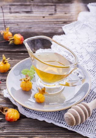 chicouté: Cloudberry honey in a gravy boat on a saucer with ripe berries arctic cloudberries on a simple wooden background with vintage cloth embroidery Banque d'images
