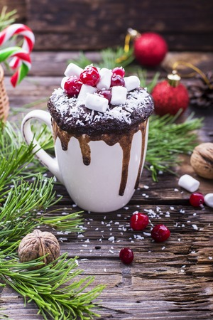 christmas paste: Mug cupcake New Year Christmas with marshmallow and juicy cranberries on a wooden background with toys and pine branches. Holiday breakfast Stock Photo
