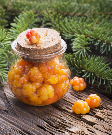 chicouté: Juicy ripe cloudberry northern and sugar in a small glass jar on a wooden background