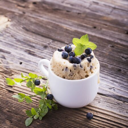 blueberry muffin: Healthy breakfast. Fresh homemade mug cake with forest blueberries in a white ceramic bowl with a sprig of ripe berries on the gray wooden background. selective focus