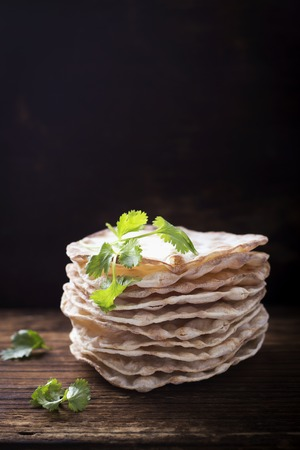 Tower thin crispy loaves of useful home cakes with chick-pea flour for home vegetarinskogo and healthy eating. On a dark wooden background with sprigs of coriander and chickpeas dry. selective focus Standard-Bild