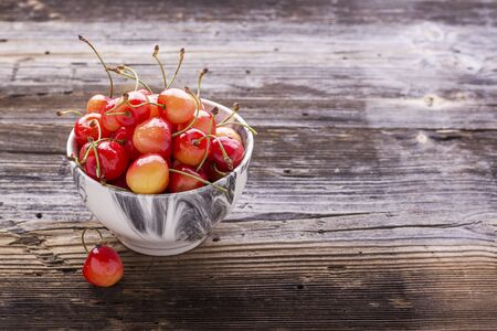 Ripe yellow cherries in a gray marble bowl on a wooden background. selective focus Stock Photo