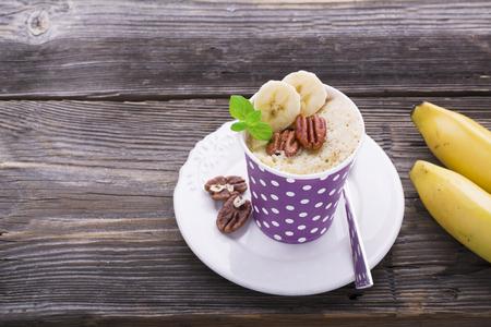 microondas: desayuno rápido en el microondas durante cinco minutos. Tortas de la taza del plátano caseras en vasos de papel para la merienda en porciones. dos porciones con pacanas y rodajas de plátano, menta fresca