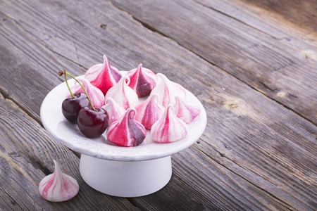 Modern fashion trend fruit meringue with pink watercolor drawings. Preparation for a Eton mess with cream, ripe cherries in portioned cups for festive sweet table. selective focus Stock Photo