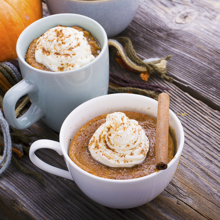 Quick meal breakfast snack in the microwave. Fragrant homemade pumpkin pie fall for five minutes in the cup portions with whipped cream and cinnamon on a wooden background. selective focus