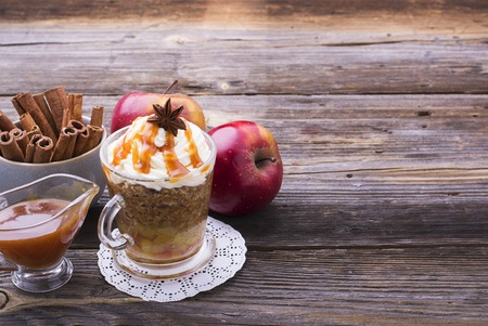 caramel sauce: Quick breakfast snack for a few minutes in the microwave. Traditional apple pie in a mug with whipped cream quickly caramel sauce in a transparent mug on a high wooden gray background. selective focus Stock Photo