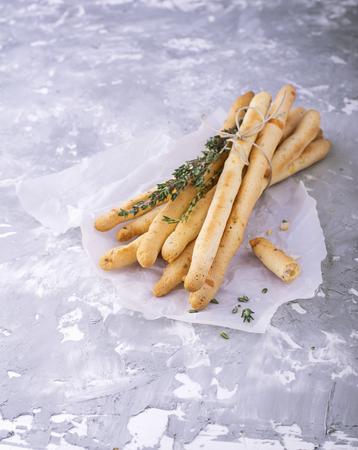 gressins: Frais faits maison baguettes de pain croustillant avec le thym et le sel de mer sur fond de béton gris avec des herbes fraîches. mise au point sélective