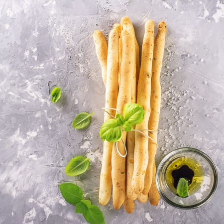 Fresh homemade crispy bread sticks with thyme and sea salt on a gray concrete background with fresh herbs. selective focus