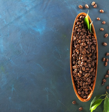 coffeetree: Wooden plate in the form of boats full of dark aromatic coffee beans on a colorful blue-green background. Top view