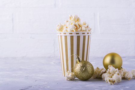 Salty fresh crusty homemade popcorn in silver paper cup in the fashion light background of white brick wall in a New Years interior with silver Christmas balls. selective focus Stock Photo