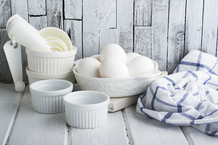 selective focus: Ceramic white form for baking and village eggs on the kitchen simple white wooden background with blue dining cotton towel. Horizontal. selective focus