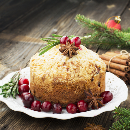 Fragrant homemade muffins with cranberries, candied fruits soaked in brandy, herbs and spices on a wooden dark background. Served with rosemary. selective focus Stock Photo