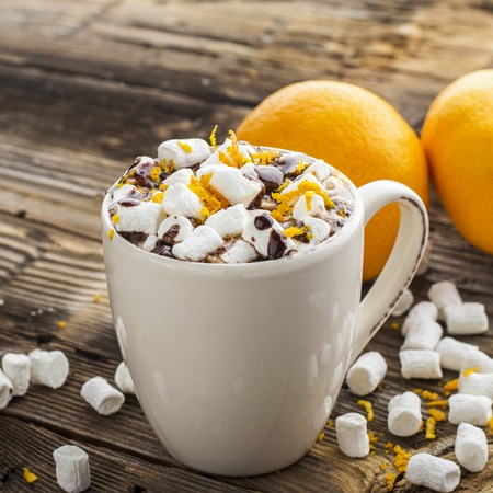 A cup of hot cocoa with chocolate orange and orange zest on a dark wooden background. selective focus