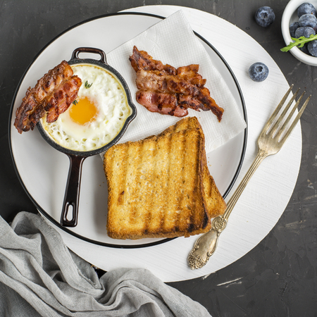 Breakfast set. Pan of fried eggs with bacon and fresh blueberries on black background, top view