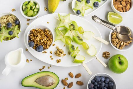 brochetas de frutas: Healthy fresh cheerful breakfast for the whole family: Fruit skewers green, granola, a bowl of quinoa, nuts, berries, avocado. Top view. Color year.