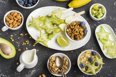 brochetas de frutas: saludable desayuno fresco. Granola, cuenco quinua, varias nueces y frutas pinchos con frutos verdes sobre un fondo oscuro. Vista superior. año color. Verdor. Parte superior Foto de archivo